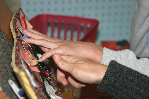 A child's hand explores a tactile calendar using hand-under-hand with another individual guiding them over the various symbols.